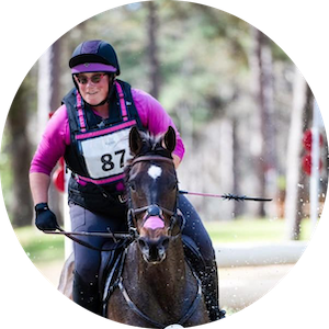 Lauren Romanelli galloping her bay horse on cross country wearing a pink shirt
